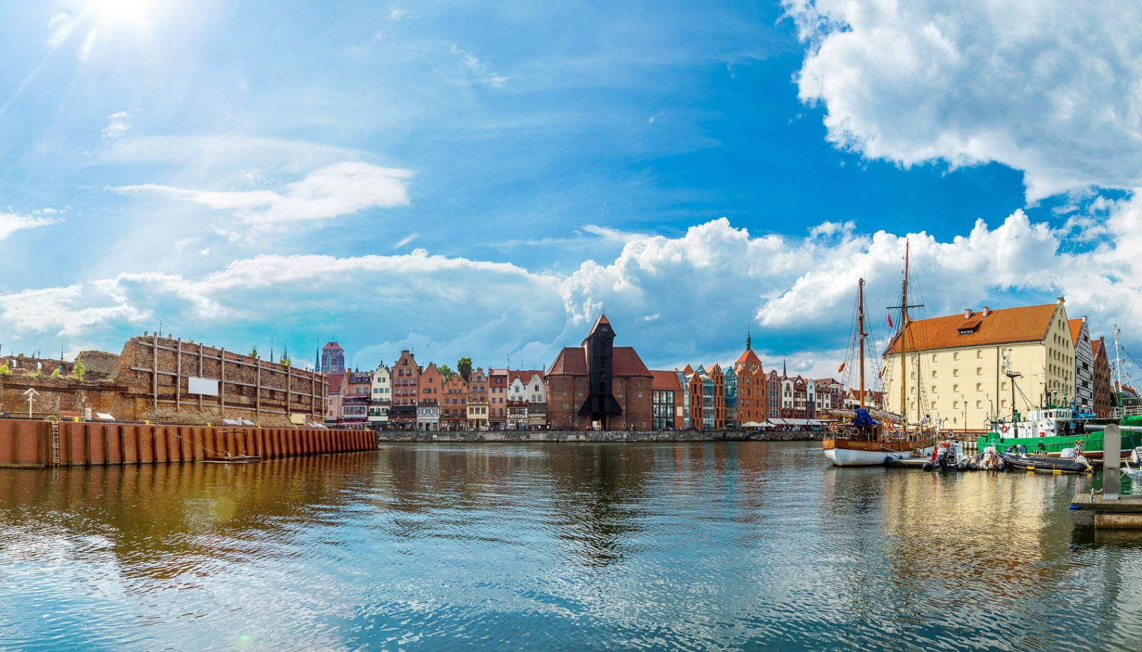 Tourist ship and historic houses next to Motlawa river in port of Gdansk, Baltic Sea, Poland.